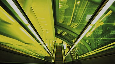 Neon yellow and lime green lights along a descending escalator